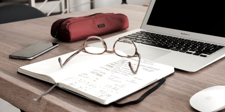 An open diary with the owner's glasses on top of it, on a table, by a laptop, cell phone and pencil case.