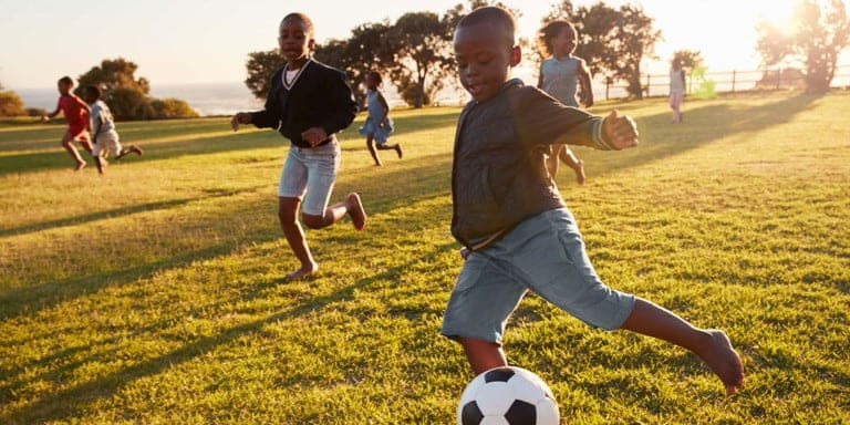 A group of young children running, having fun and kicking a soccer ball in a green field with the sun shining in the background.