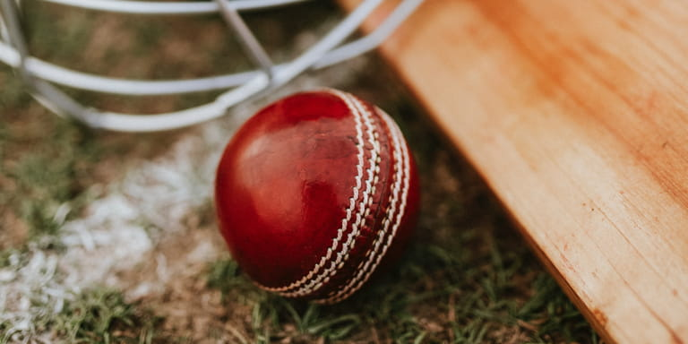 Red cricket ball lying next to a cricket bat on green grass of cricket pitch.