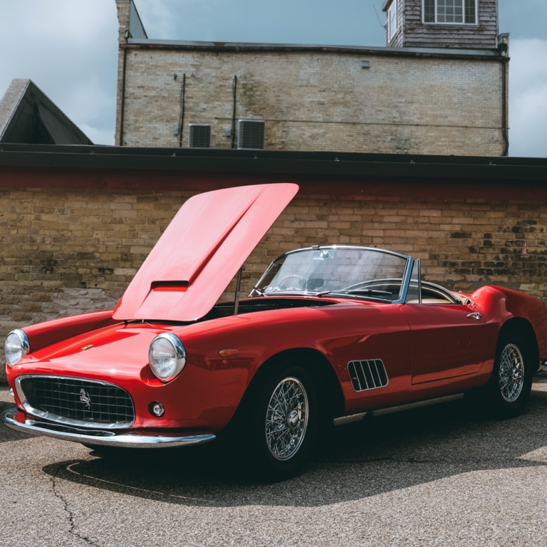 Red, vintage, cabriolet Ferrari sports car with it's top down is parked diagonally next to a brick wall with it's hood up.