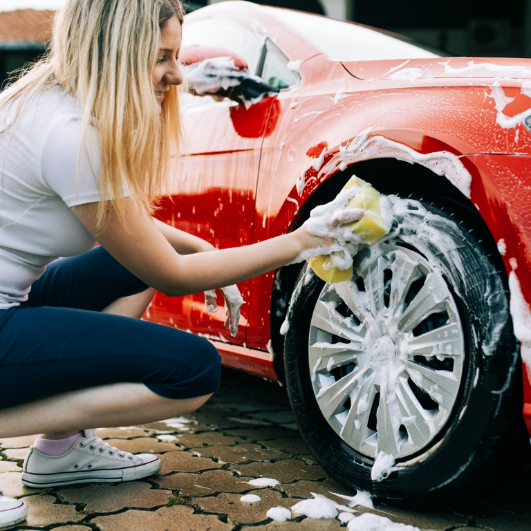 A lady in jeans and a white t-shirt with loose mid-length blonde hair squatting and washing the rims on her red car.