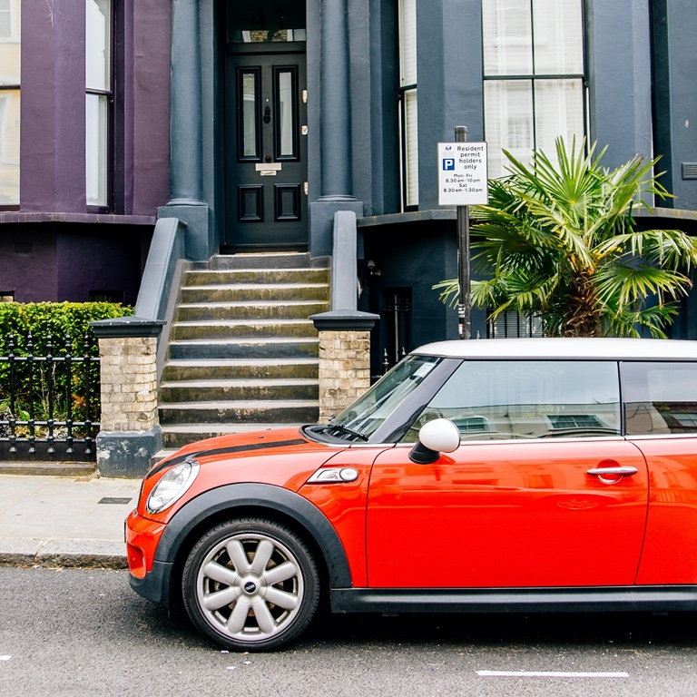 A red Mini Cooper coupe parked on the side of the pavement of an apartment building.