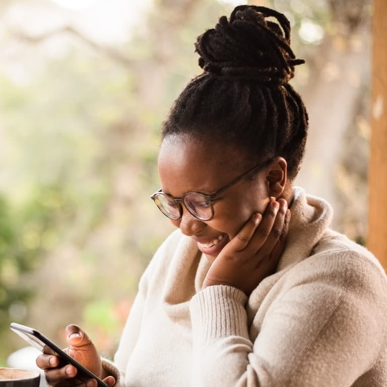 Young lady smiling while engaging FinEazy's chatbot on her cell phone.