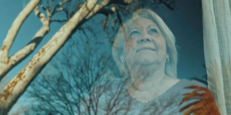 An elderly woman with grey hair stands looking out her window looking at the bare branches of the trees.