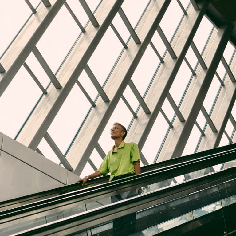 A man in glasses and a green golf t-shirt holds the rails of the escalator with his right hand, as it is coming down.