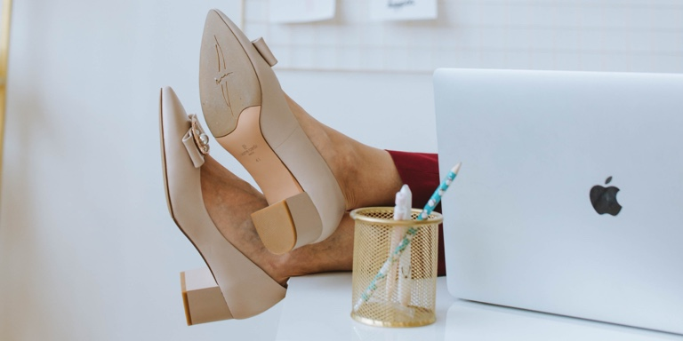 A woman's feet placed on the table next to a laptop and a pencil container