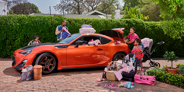 Husband surprises his family with a new orange coupé sports car which is parked in the driveway of their family home. The wife is frustrated as they try to fit their luggage into the compact sports car.