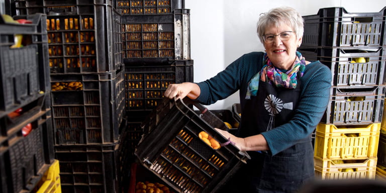 #NoApologyForMySuccess Ina Lessing, entrepreneur and business woman, standing holding a crate filled with fresh fruit ready to be made into delicious jams.