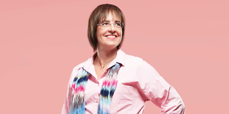 Professor Jackie Smilg wearing a pink shirt and a scarf.
