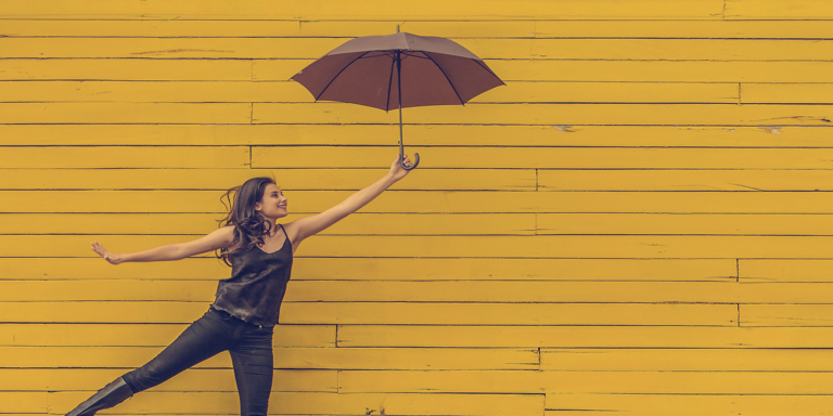 Young girl holding a red umbrella against a yellow wall. She's smiling and is confident about her journey to success.
