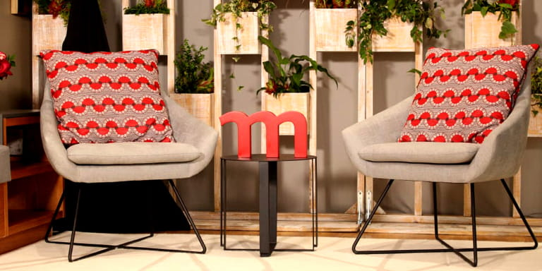 Two grey chairs with vibrant red and grey cushions on them.