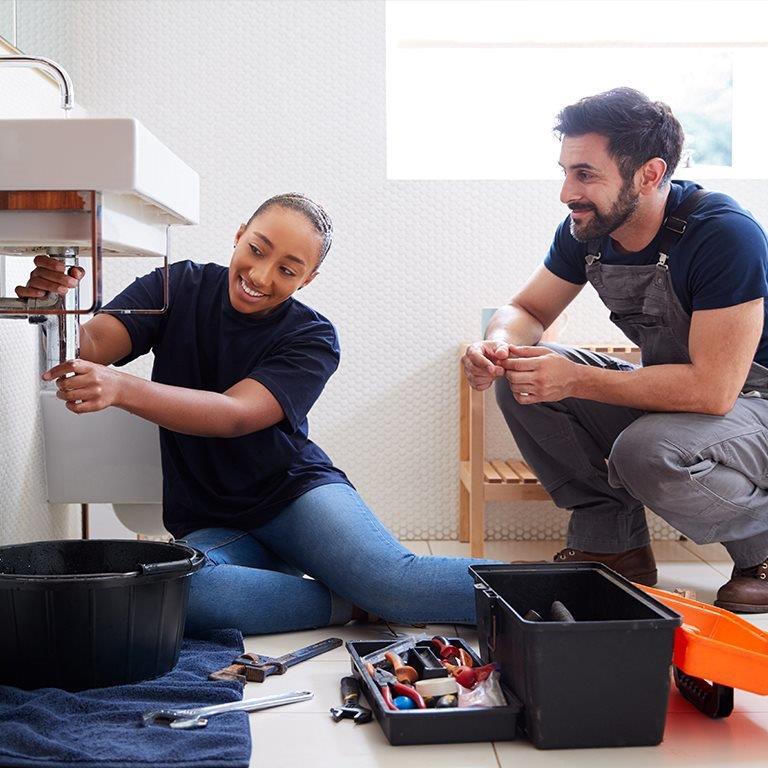 A couple fixing a bathroom sink