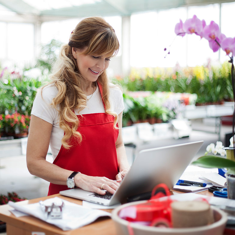 A lady standing in a nursery with flowers in the background working on a laptop, wearing a red apron.