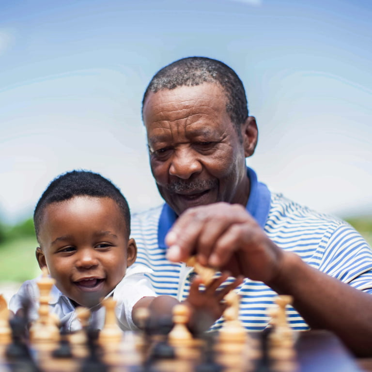 An old man enjoys retirement playing chess with his toddler grandson.