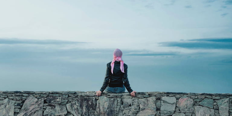 A lady wearing a black leather jacket and blue jeans and a pink bandana wrapped around her head sitting on a stone wall looking at the cloudy horizon in front of her.