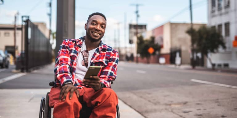 A young man in orange trousers and red checkered jacket sitting in a wheelchair in an empty street, smiling.