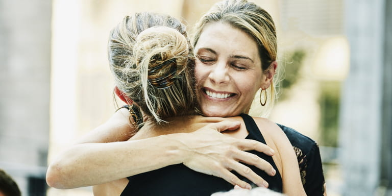 Two ladies hugging and smiling.