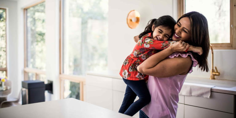 A young mum hugs her daughter excitedly in the kitchen of their home.