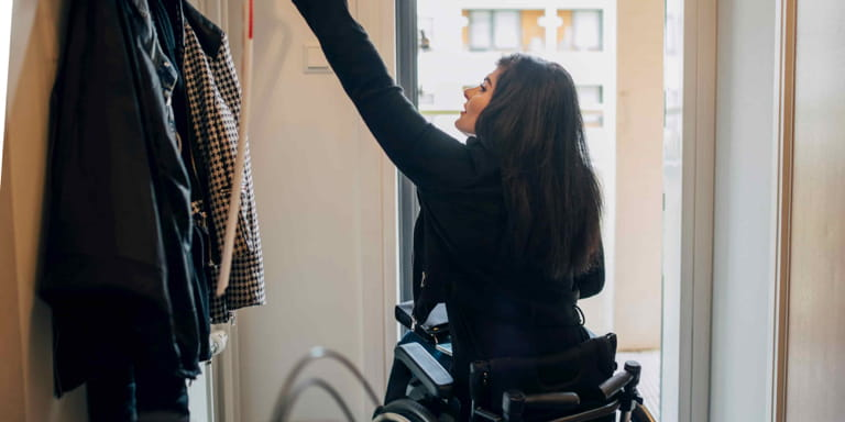 A young female wearing black is sitting in a wheelchair reaching up to grap her coat from the rack as she is about to leave the building.
