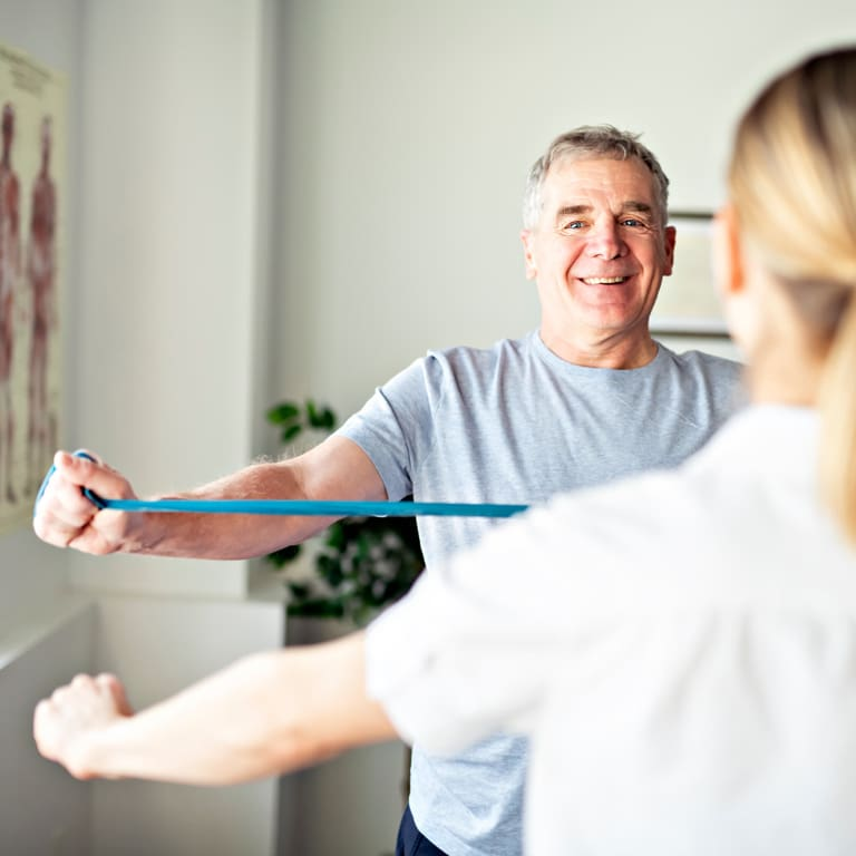 An older male using a resistance band for resistance training whilst training with his female personal trainer.