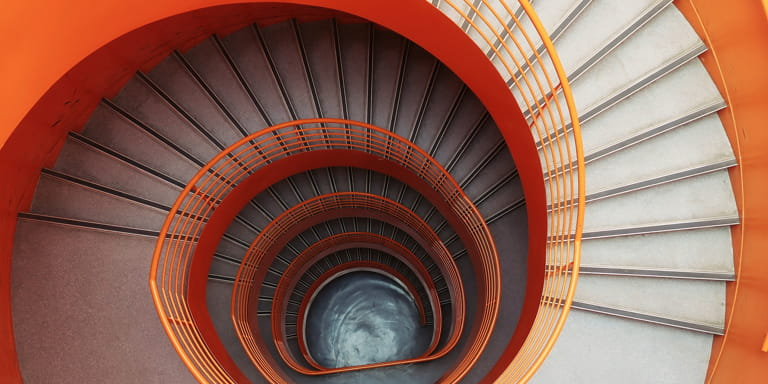 Spiral staircase with vibrant orange walls and washed grey stairs from a birds eye view.