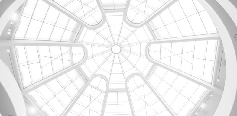 A flower-shaped view of a glass ceiling with white steel beams holding the structure.