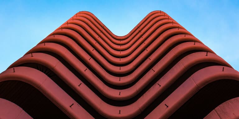 An abstract, high-rise, curved red building of a financial institution, against a blue sky backdrop.
