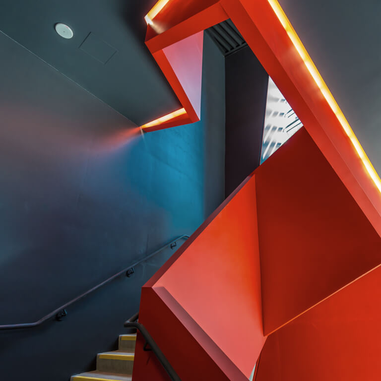 A staircase in a modern office building with an abstract, red and geometric balustrade.