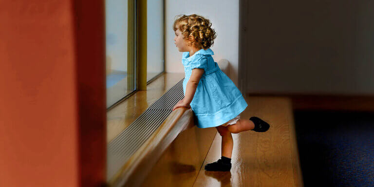 Toddler in blue dress looking out the window to symbolise looking ahead at the prospect of a bright financial future.