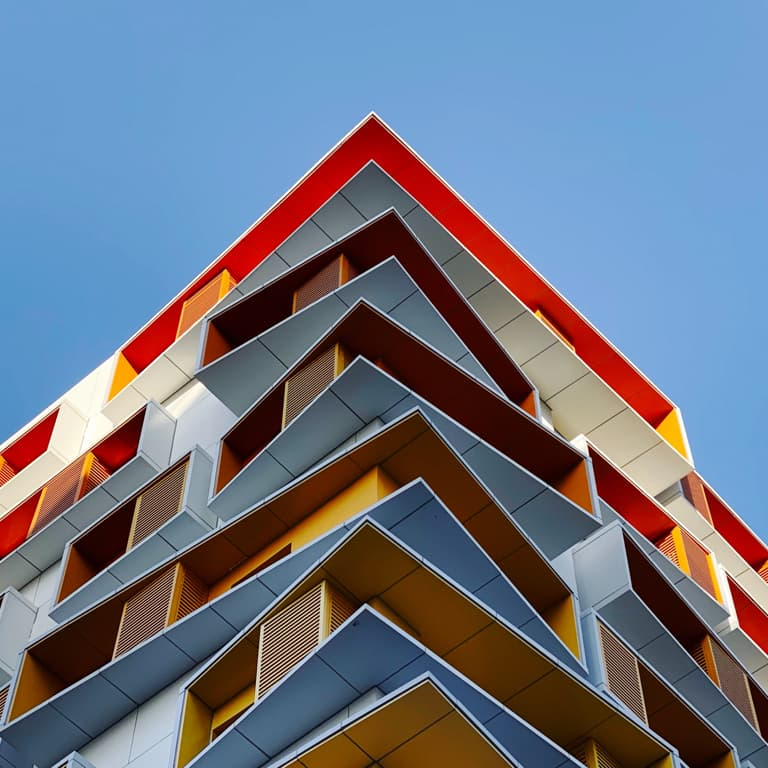 A shot of a sharp corner of a multistory building with protruding balconies.