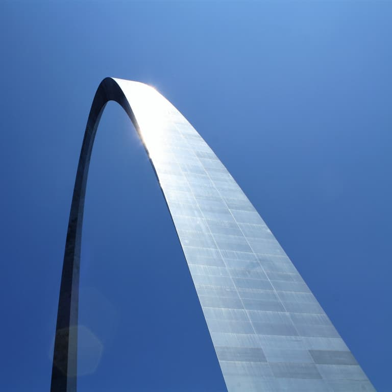 A high rising and arching silver steel structure with a blue sky background.