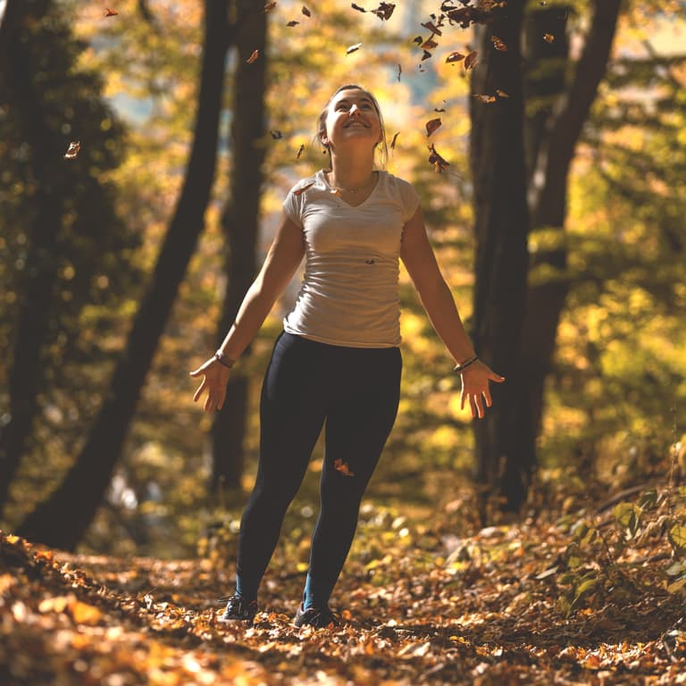 A lady jumping joyfully amongst trees with autumn leaves falling to the ground.