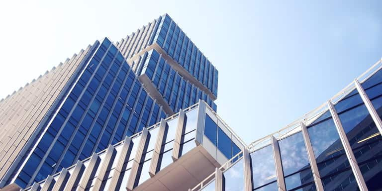 A contemporary and geometric blue glass office building made of asymmetric blocks.