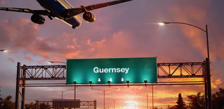 A plane flying low above a billboard, directing traffic towards Guernsey, at dusk.