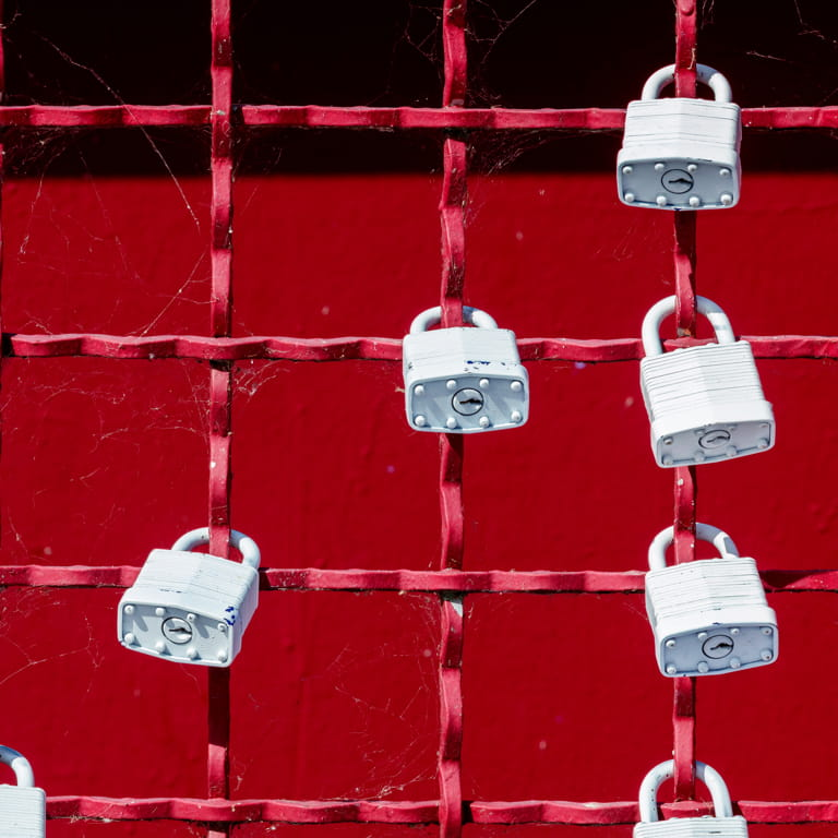 Red grid wire fence with nine white heavy duty padlocks fastened on numerous grids.
