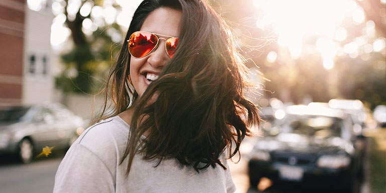 Young brunette woman wearing sunglasses, smiling and crossing the street, with the sun shining brightly in the background.
