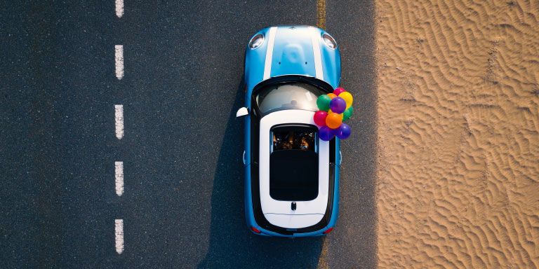 An aerial shot of a blue Mini Cooper with white stripes, driving on the open road with a bunch of colourful balloons tied to the car and blowing in the wind.