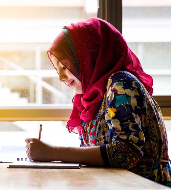 Young lady wearing a headscarf and a colorful dress sitting at a table and writing in a book. She is smiling knowing her estate administration will be handled professionally.