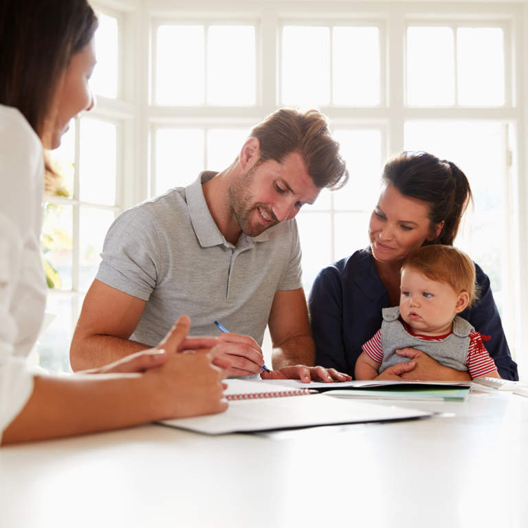 Couple with a baby and the father signing financial documents with a financial advisor.