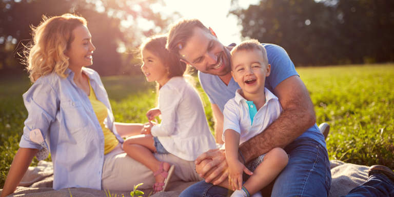 Mom, dad and two kids sitting on the grass at a park laughing during a sunny day.