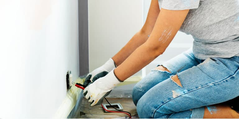 Woman wearing jeans, t-shirt and working gloves sitting on the floor in front of a plug checking the electrical outlet for a current using a multimeter.