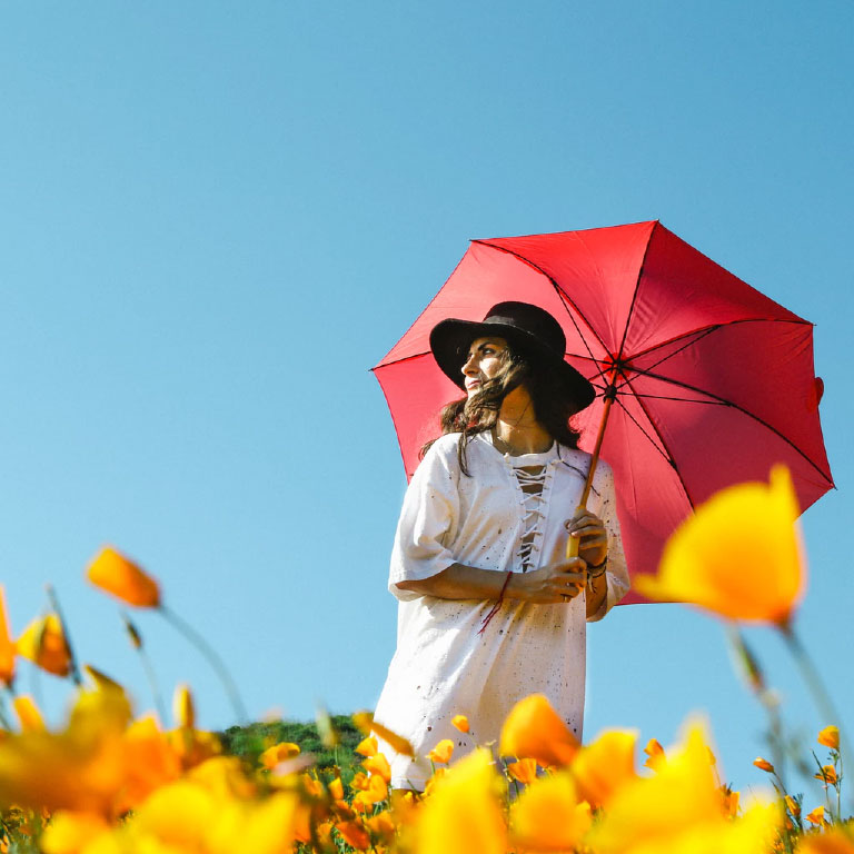 Happy, young woman wearing a summer cotton dress and walking in a meadow of yellow flowers while holding a red umbrella.