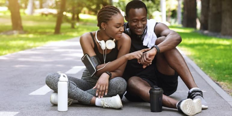 Leading a healthy lifestyle, an athletic lady in a red sporting gear, holding her cell phone with earphones in her ears with stairs in the background.