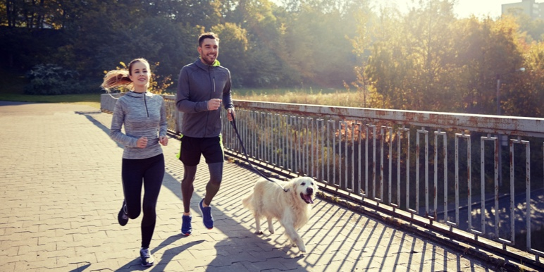 Young lady at a market, wearing a sun hat, having some fun and holding a strawberry in front of each of her eyes.