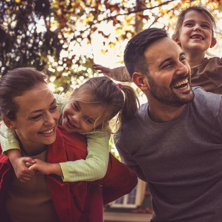 Woman wearing a blue and white vintage dress sitting on the grass holding a plate of healthy strawberries.