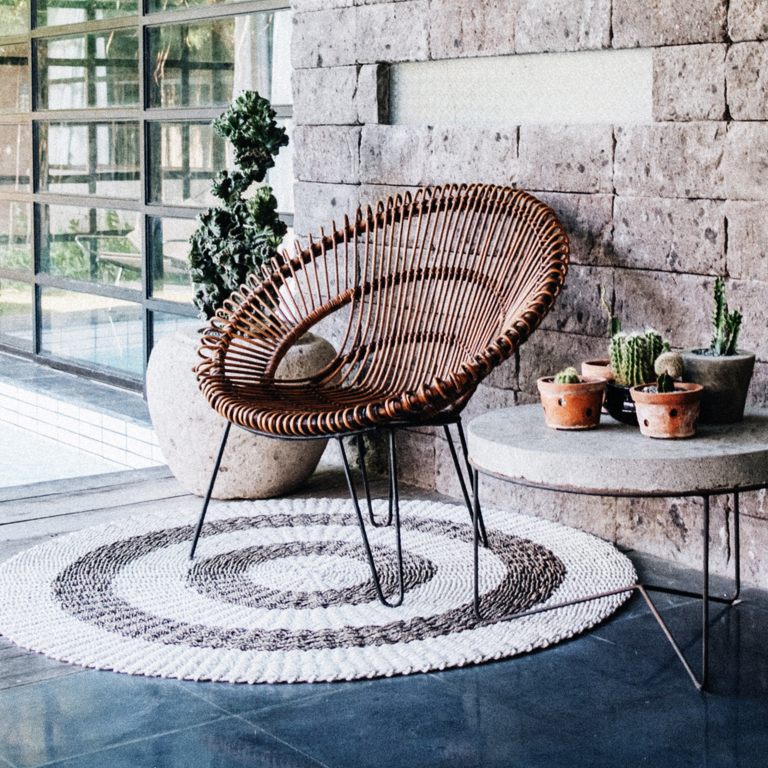 Cane chair on a grey and white coloured round carpet, next to a concrete table with metal legs that has a range of cacti plants displayed on it.