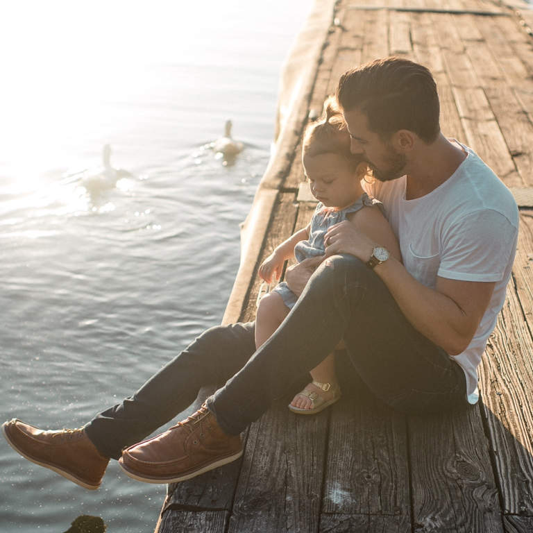 Cute little baby girl sitting on her dad's lap on deck by a lake, watching the ducks swimming by.