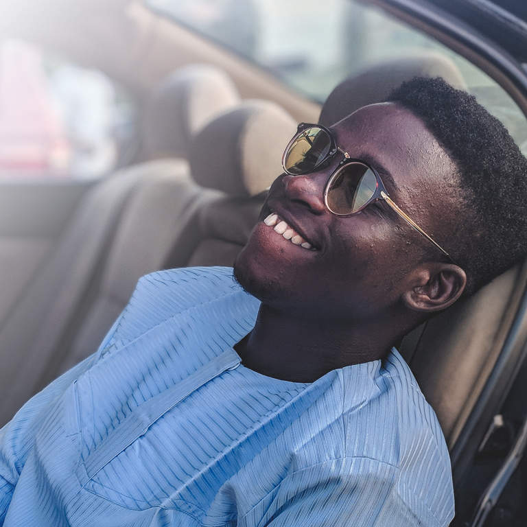 A relaxed young man sitting in the back seat of a car, wearing sunglasses and smiling.