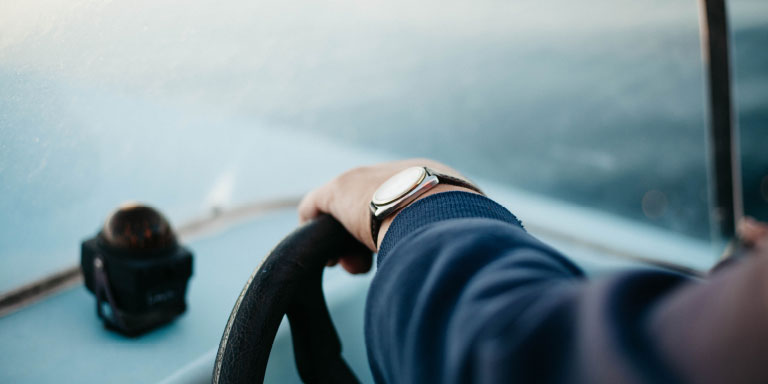 Close up of a man's arm resting on the steering wheel of his car with a camera on the dashboard. He is wearing a watch and long-sleeved blue suit jacket.
