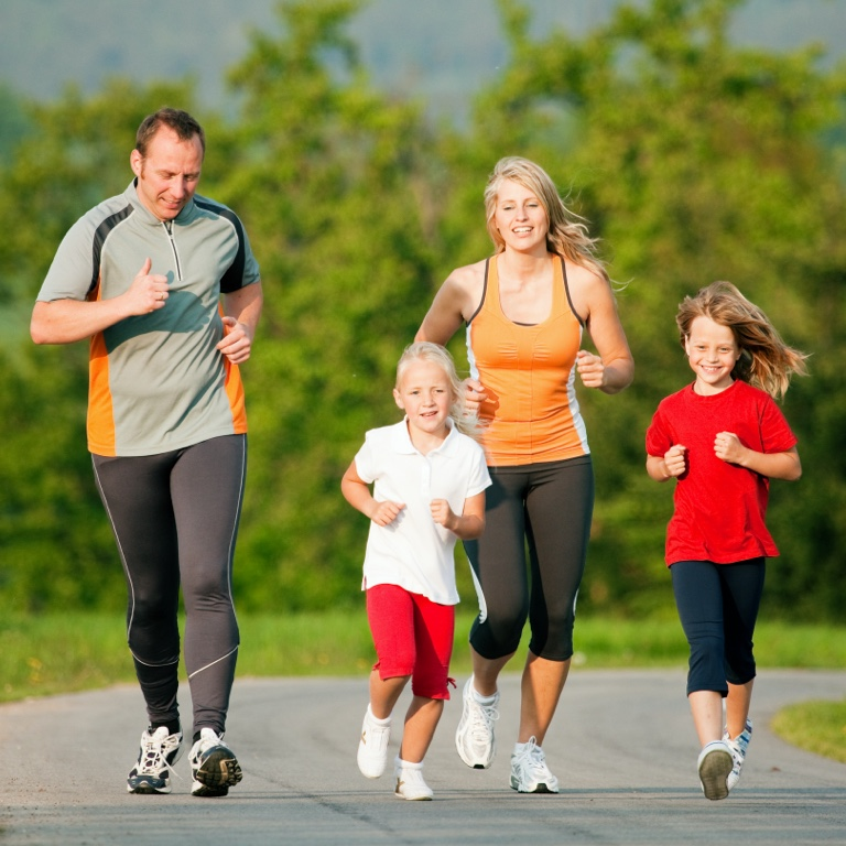 Young male musician wearing glasses and smiling while playing a guitar. His guitar has a string of fairy lights on it.